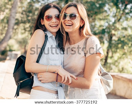 Two young women walks and laugh in city. Polaroid colors - stock photo