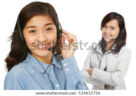 Two young women wearing headsets (on white background) - stock photo