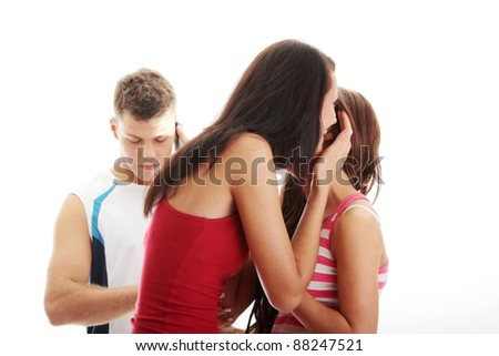 Two young women whispering about a man standing in background. Isolated on white - stock photo