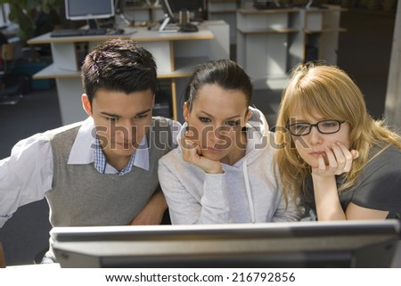 Two young women with a young man using a computer