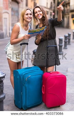 Two young women with baggage checking route outdoors - stock photo