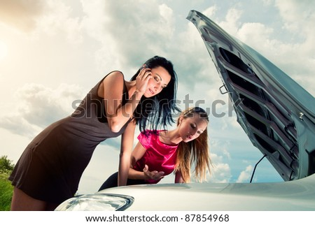 Two young women with broken car on a road - stock photo