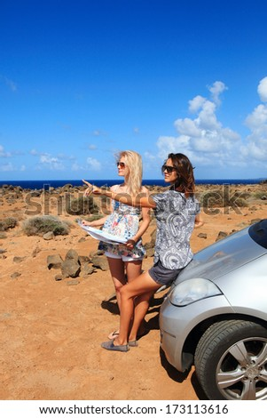 Two young women with car look at road map on a beach against sea and sky  - stock photo