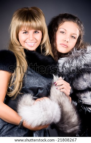 Two young women with fur coats. On dark background. - stock photo