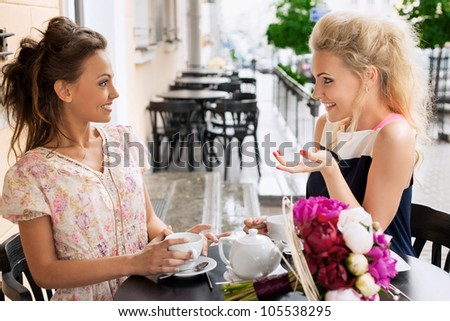 Two young women with great smile and hairstyle sitting at a bar, drinking tea and coffee.
