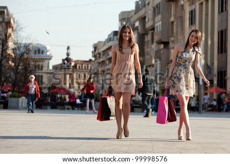 two young women with shopping bags walking in the city - stock photo