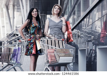 Two young women with shopping cart - stock photo