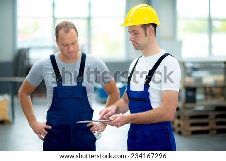 two young worker in factory using tablet pc - stock photo