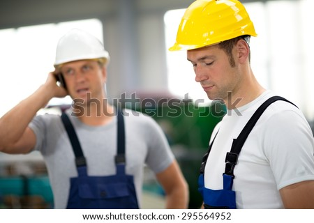 two young worker in factory with hard top - stock photo