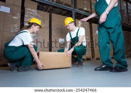 Two young workers lifting heavy box in warehouse - stock photo