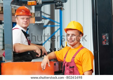 two young workers men in uniform at warehouse with forklift facilities - stock photo