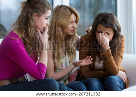 Two young worried girls supporting crying friend - stock photo