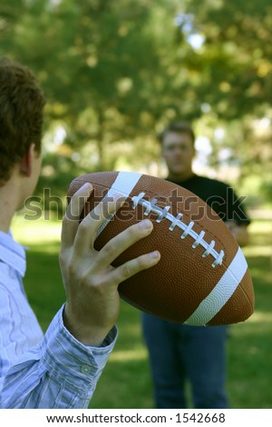 Two younger men playing a game of football, as one holds football in his hand about to throw it to the other man
