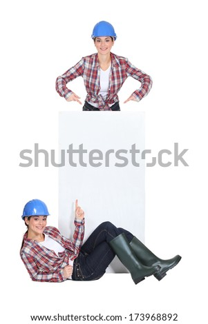 twosome of jovial girls with blue hard hat - stock photo