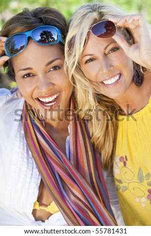 Twp beautiful young women in their twenties laughing and having fun on vacation, shot in golden sunshine in a tropical resort location. - stock photo