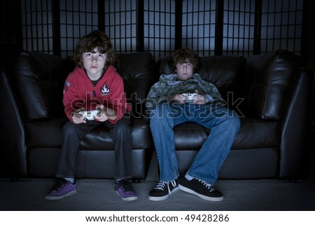 Twp boys sitting on a couch playing video games - stock photo