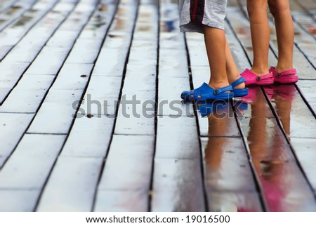 Twp kids on a wet seaside wooden deck - stock photo