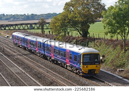 TWYFORD, UK - OCTOBER 3: A First Great Western suburban stopper service passes Twyford cutting en route to London on October 3, 2014 in Twyford. FGW operate at 208 stations over a distance of 2130 km  - stock photo