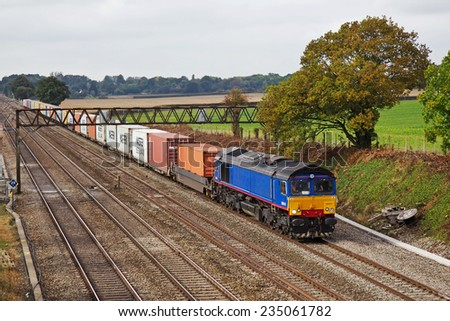 TWYFORD, UK - OCTOBER 3: A Freightliner operated intermodal mixed box train from Southampton passes Twyford on October 3, 2014 in Twyford. Freightliner operate a fleet of 80 locos & 1400 wagons  - stock photo