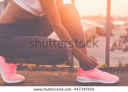 Tying shoelaces. Close-up of young woman in sports clothing tying her shoelaces while standing on the bridge with evening sunlight and urban view in the background - stock photo