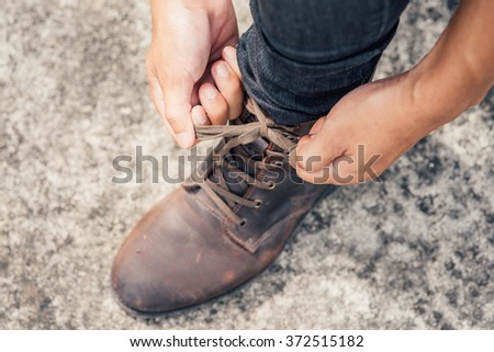 Tying Shoes on cement floor, Men fashion brown leather boots - stock photo