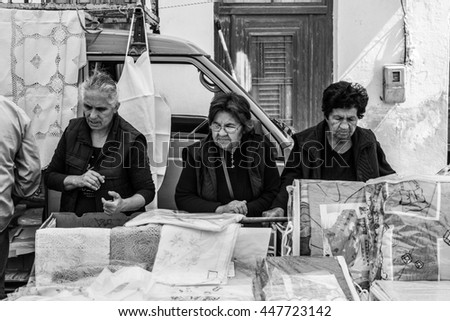 TYMBAKI, CRETE - APRIL 22. Three women on the farmers market in Tymbaki in the south-central of Crete on April 22, 2016. The older Ladies have a look for the quality of the products