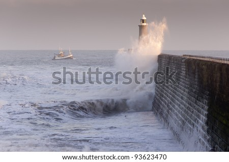 Tynemouth north pier and boat / Waves crashing against Tynemouths pier and lighthouse with fishing boat heading for safety - stock photo