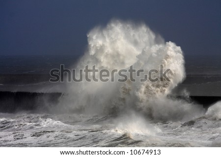 Tynemouth Pier and rough winter stormy weather with breaking waves - stock photo