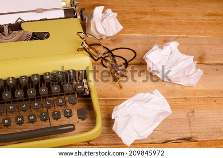 Typewriter and rumpled pieces of paper, a concept - stock photo