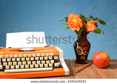 Typewriter apples and flowers in a vase on the table - stock photo