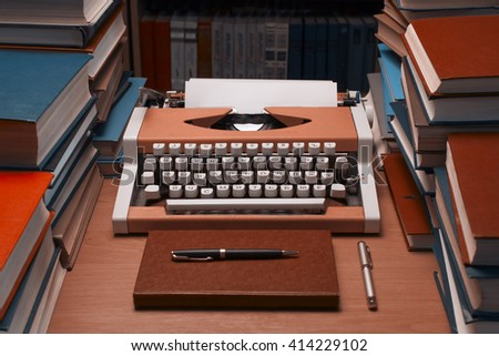 Typewriter with blank sheet of paper with many books in background and  beside - stock photo