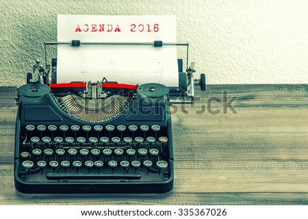 Typewriter with white paper page on wooden table. Sample text AGENDA 2016. Vintage style toned picture - stock photo