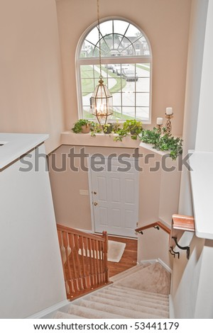 Typical American house with a two story entry foyer and carpeted staircase. - stock photo