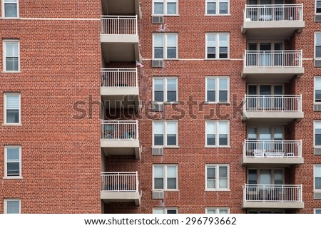 Typical apartment building exterior with brick, windows and balconies - stock photo