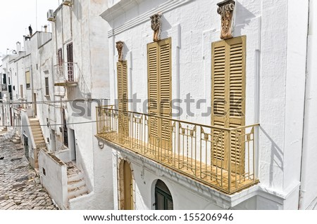 Typical back alley of Ostuni's old town in Apulia. It's called also the white town. - stock photo