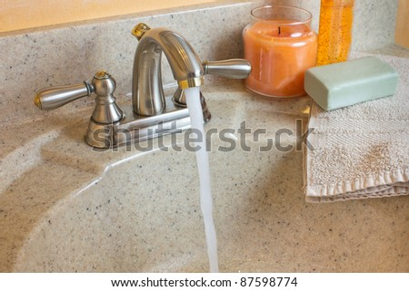Typical bathroom sink with running water and soap, candle and cloth on the counter - stock photo