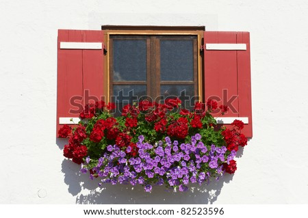 Typical Bavarian Window With Open Wooden Shutters, Decorated With Fresh Flowers - stock photo