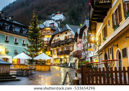 Typical Buildings with Christmas Decorations in Small Mountain Village on a Rainy Night. Hallstatt, Austria.