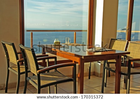 Typical Cafeteria in Majorca at sunset with wooden furniture and windows facing the coast landscape - stock photo