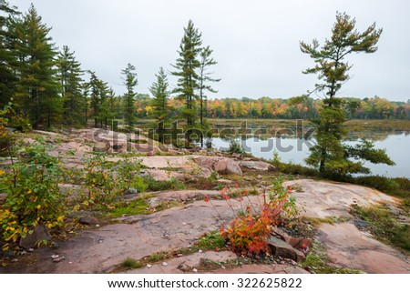 Typical Canadian landscape of a lake at Killarney Provincial Park with multicoloured fall trees and red rock formations - stock photo