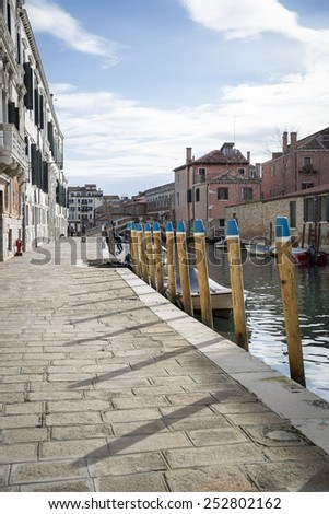 Typical canal bank with mooring poles, Venice, Italy - stock photo