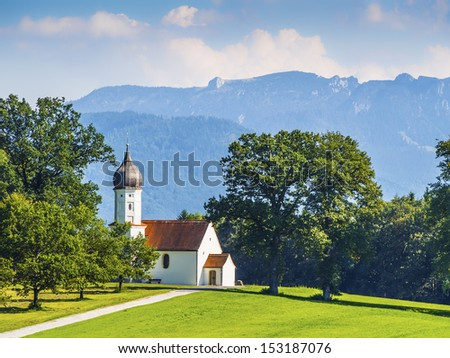 Typical chapel on green meadow with trees and mountains in Bavarian alps