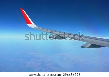 Typical classic view through aircraft window onto airplane wing and wingtip. - stock photo