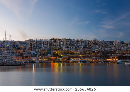 Typical colorful evening scenery in the Mikrolimano marina in Athens in the afternoon, with clouds over the city lights and many restaurants on the seafront in Greece Long exposure photography - stock photo