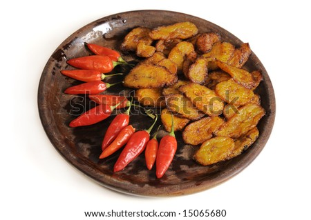 Typical cuban food on wooden dish isolated - fried banana and chili peppers
