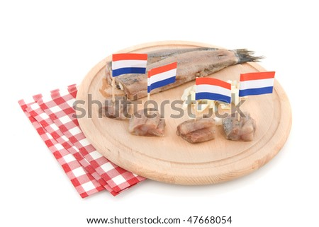 Typical Dutch herring with flags on wooden plate - stock photo