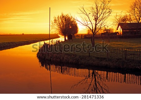 Typical dutch landscape in the countryside from the Netherlands at sunset - stock photo
