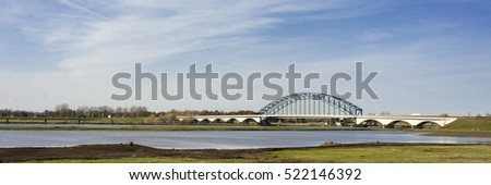 Typical Dutch river IJssel landscape with blue sky, white clouds, wind and sunny weather