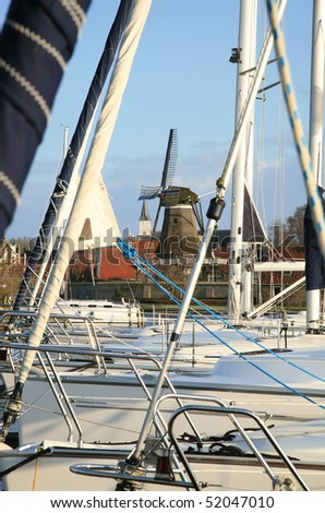 Typical Dutch view. Marine with sailboat and old, traditional windmill in Sloten, small town in Netherlands.