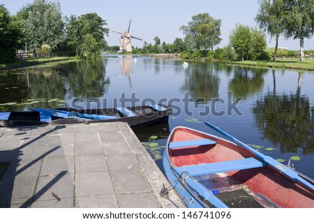 Typical Dutch vista with boats for rent and a mill in Klein Giethoorn in Hazerswoude, Netherlands.